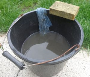 Bucket half filled with murky water from loft tank